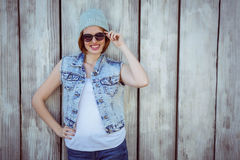 Smiling hipster woman wearing a beanie hat. Smiling hipster woman in sunglasses and a beanie hat against a wooden background royalty free stock photos
