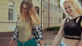 Smiling hipster womans running at city street. Cute girls have fun outdoors stock video footage