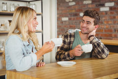 Smiling hipsters talking and enjoying coffee together Stock Photography