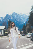 Smiling hiptser girl on mountain background. Young woman traveler wearing white casual shirt smiling on road royalty free stock photos