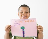 Smiling hispanic boy holding drawing. Royalty Free Stock Images
