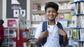 Smiling hispanic boy at school. Portrait of smiling hispanic boy looking at camera. Young elementary schoolboy carrying backpack and standing in library at stock video
