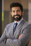 Smiling Hispanic businessman, arms crossed, close up vertical Royalty Free Stock Photos