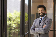 Smiling Hispanic businessman with arms crossed, to camera stock photography