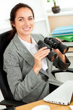 Smiling hispanic businesswoman holding binoculars Stock Images