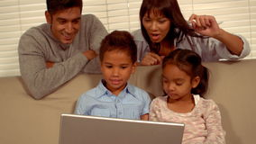 Smiling Hispanic family on a computer. At home stock video