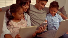 Smiling Hispanic family on different devices. At home stock footage