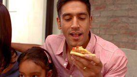 Smiling Hispanic family eating pizza in living room stock footage