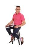 Smiling Hispanic man sitting on chair. Stock Image