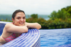 Smiling hispanic woman in pool. Smiling hispanic woman portrait in pool. Girl in outdoor jacuzzi Stock Photos