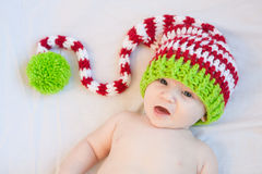 Smiling Holiday Baby. Baby wearing red white and green striped knit hat Stock Image