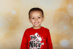 Smiling holiday boy. Young boy standing in studio, smiling with red shirt and bokeh background Royalty Free Stock Photos