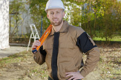 Smiling home inspector holding level at construction site Stock Photography