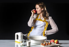 Smiling homemaker sniffing apple Royalty Free Stock Image