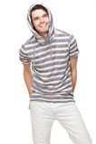 Smiling Hooded Sweatshirt Man. Smiling handsome man with hood over his head. Fashion model has hands in back pocket and wearing a striped hooded sweatshirt Stock Photo