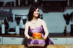 Smiling hostess holds cake like big donut with fondant Royalty Free Stock Photos
