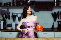 Smiling hostess holds cake like big donut with fondant. Smiling hostess holds cake like big donut with red fondant stock photography