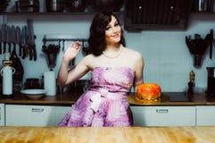 Smiling hostess holds cake like big donut with fondant Stock Photos