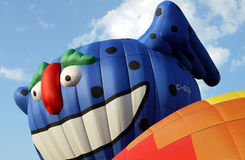 Smiling Hot Air Balloon Character. A colorful character hot air balloon rises up from a hot air balloon festival royalty free stock photography