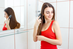 Smiling hot girl combing her hair in the bathroom Stock Images