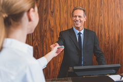 Smiling hotel manager welcoming woman Royalty Free Stock Photos