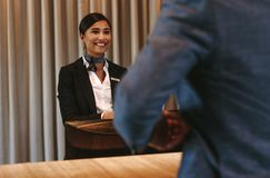 Smiling hotel receptionist attending guest at check-in counter. Smiling hotel receptionist talking with male guest at reception counter. Happy female Royalty Free Stock Images