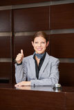 Smiling hotel receptionist holding thumbs up Royalty Free Stock Photos