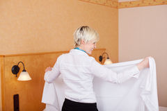 Smiling Housekeeper Making Bed In Hotel Room Stock Images