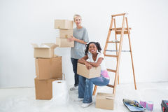Smiling housemates carrying cardboard moving boxes. And looking at camera in new home Royalty Free Stock Photos