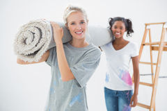 Smiling housemates carrying rolled up rug Royalty Free Stock Image