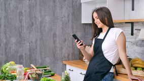 Smiling housewife chatting using smartphone cooking appetizing healthy food at kitchen