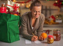 Smiling housewife with checks exploring christmas purchases Royalty Free Stock Image