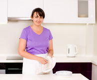 Smiling housewife cleaning the dinner plates Royalty Free Stock Photo
