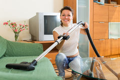 Smiling housewife cleaning sofa Royalty Free Stock Image