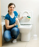 Smiling housewife cleaning toilet bowl with sponge Stock Photo