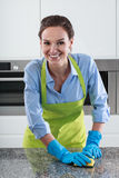 Smiling housewife cleans the worktop Royalty Free Stock Photos