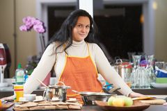 Smiling housewife cooking in her kitchen Stock Photography