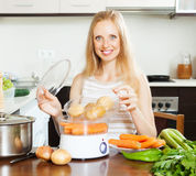 Smiling  housewife cooking potatoes with electric steamer Royalty Free Stock Image