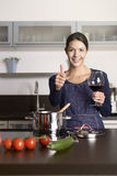 Smiling housewife giving a thumbs up Royalty Free Stock Images