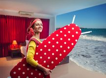 Smiling housewife with ironing-board. Happy smiling housewife with ironing-board going to the sea stock photo