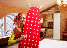 Smiling housewife with ironing-board Royalty Free Stock Photography