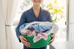 Smiling housewife keeping clean wear. Cheerful woman is holding blue green with clothes. She standing in room. Focus on apparels Royalty Free Stock Photo