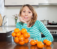 Smiling  housewife with mandarins Royalty Free Stock Photo
