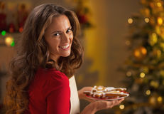 Smiling housewife with plate of christmas cookies Stock Images