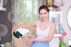 Smiling housewife posing with basket with clean laundry. stock photo