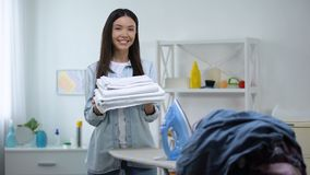 Smiling housewife standing near iron board and showing fresh linen at camera. Stock footage stock video footage