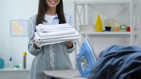Smiling housewife standing near ironing board and holding fresh linen, laundry. Stock footage stock video footage