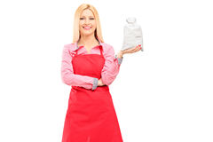 A smiling housewife wearing apron and holding a bag Royalty Free Stock Photo