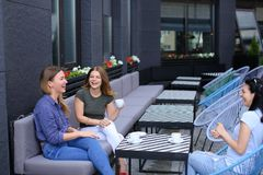 Smiling housewives meeting at cafe and drinking coffee. Concept of free time and gossips Royalty Free Stock Photo