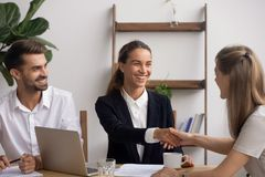 Smiling HR agent shaking hand congratulating candidate with successful interview. Smiling female senior HR agent shaking hand congratulating candidate with stock photography